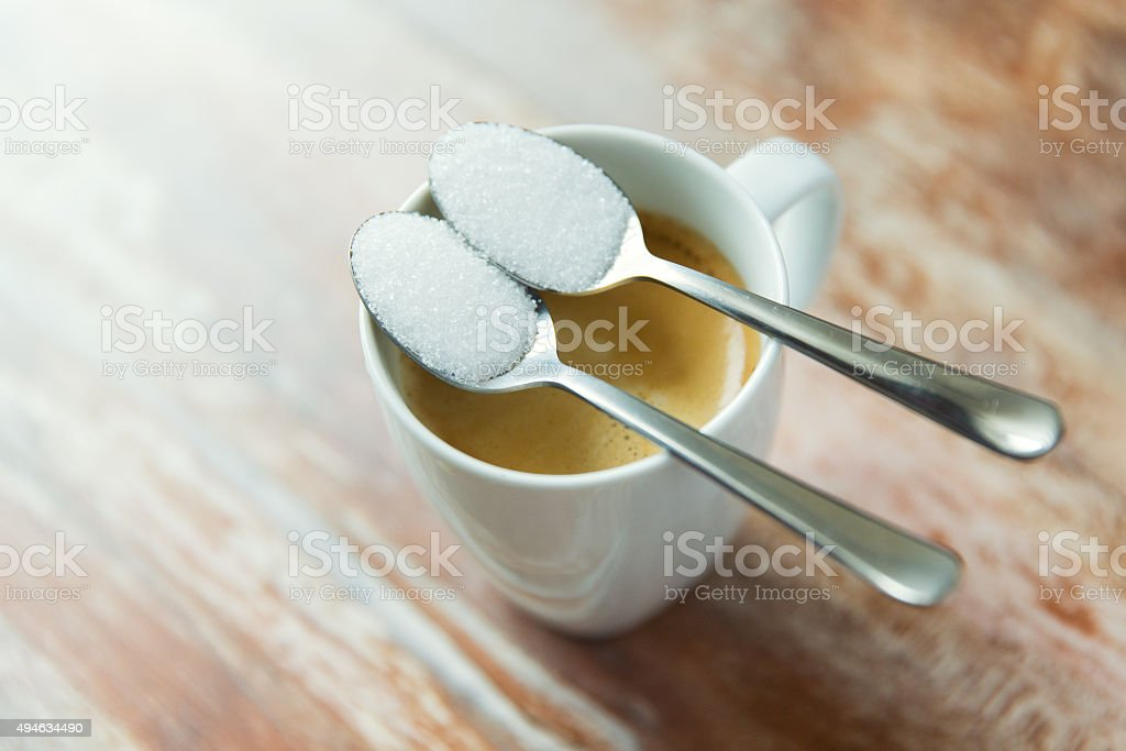 close up of white sugar on teaspoon and coffee cup stock photo