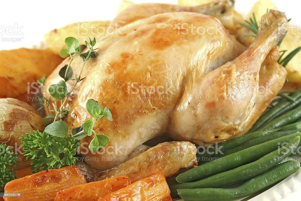 Close up of whole roast chicken and assorted vegetables royalty-free stock photo
