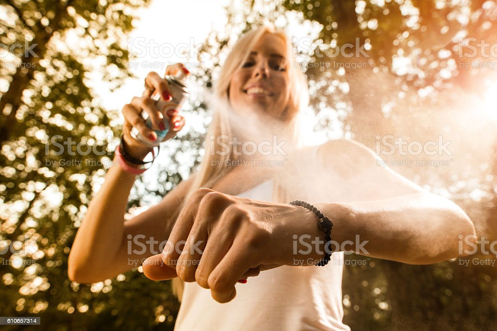 Close up of woman applying insect repellant in nature. stock photo