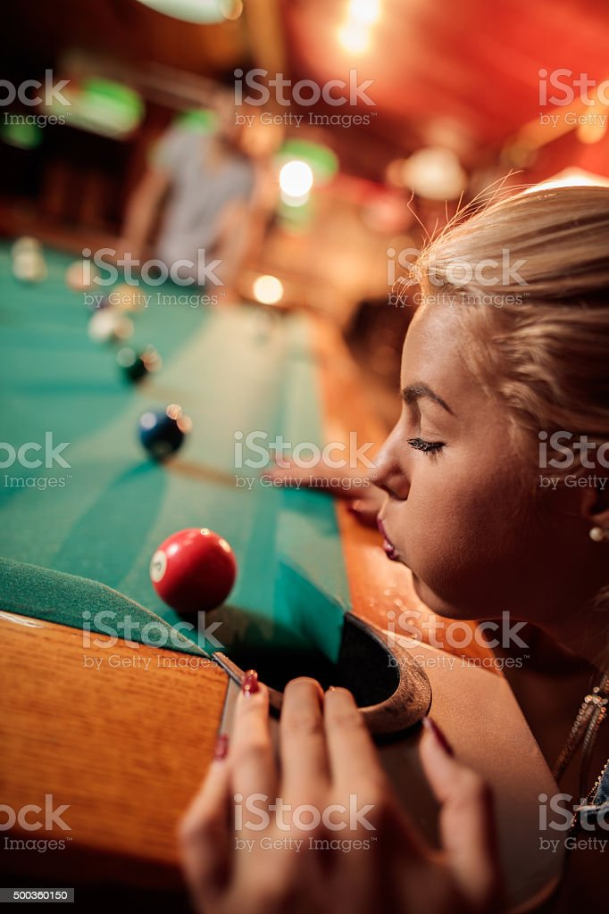 Close up of woman blowing pool ball away from hole. stock photo
