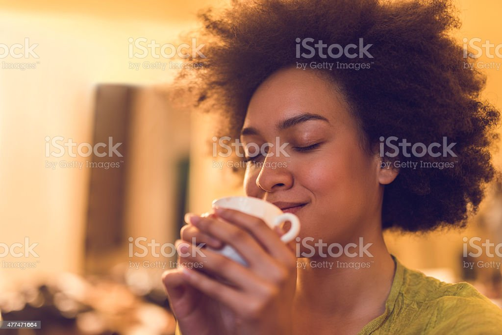 Close up of woman enjoying in a smell of coffee. stock photo