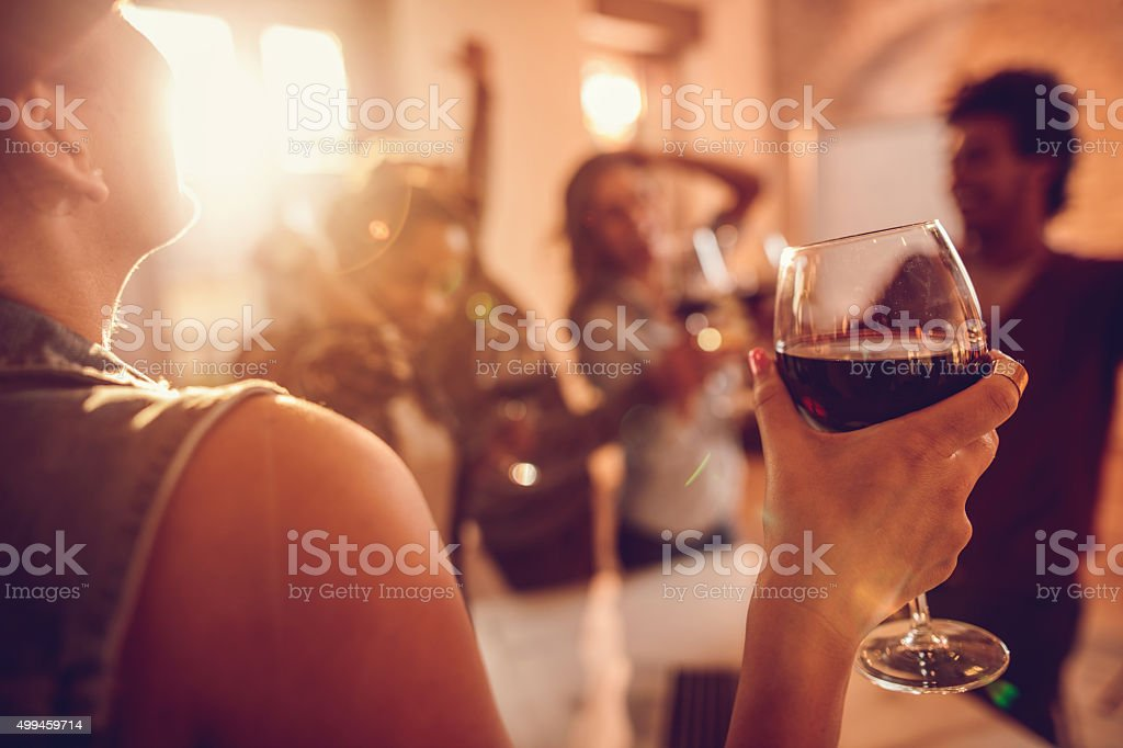 Close up of woman enjoying in wine at office party. stock photo