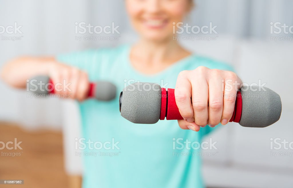 close up of woman exercising with dumbbell at home stock photo
