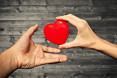 Close up of woman hand giving heart to man