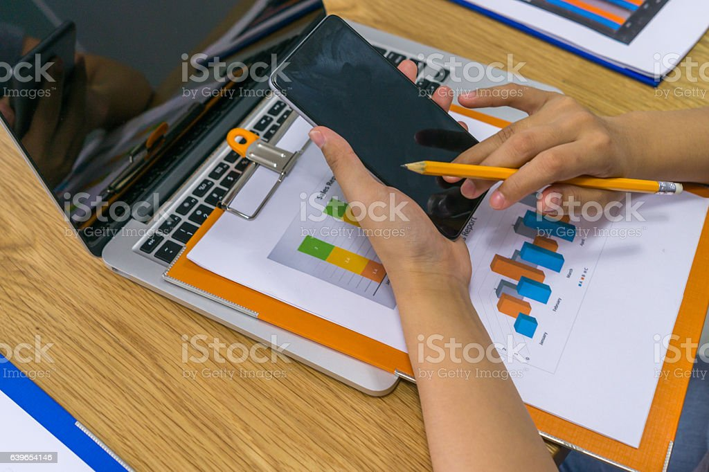 Close up of woman hand using smartphone at office stock photo