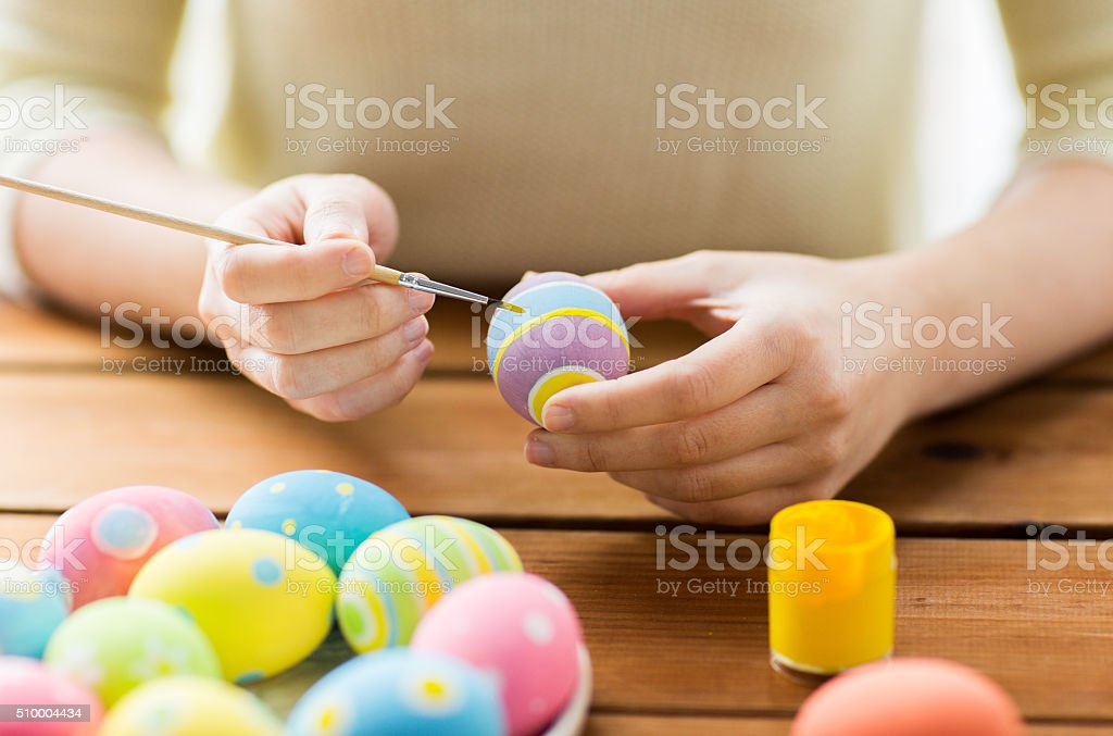 close up of woman hands coloring easter eggs stock photo