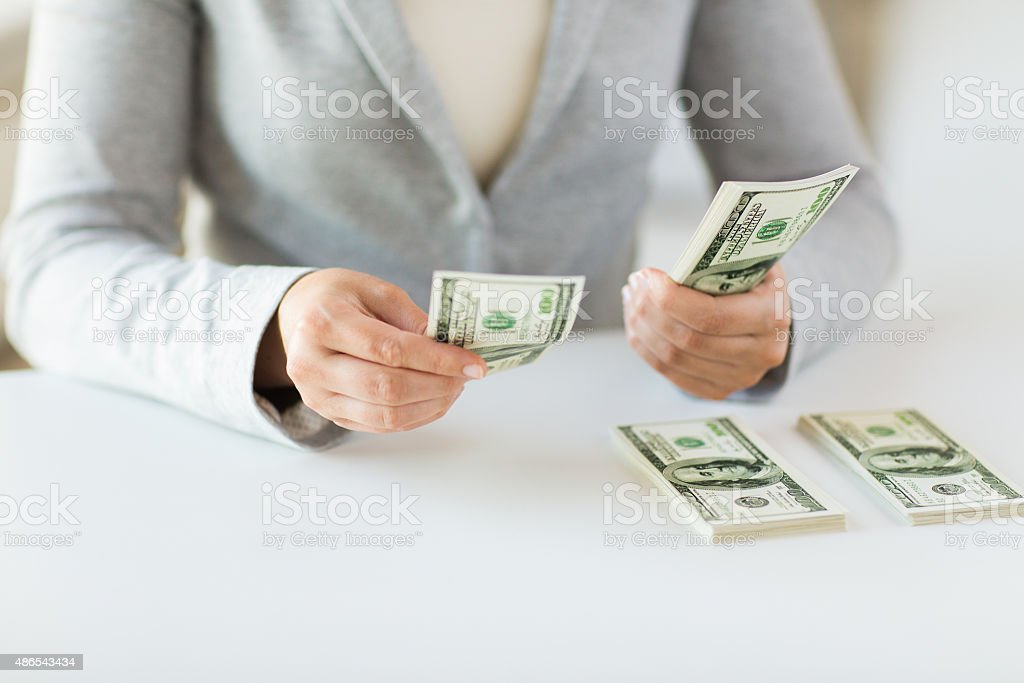 close up of woman hands counting us dollar money stock photo