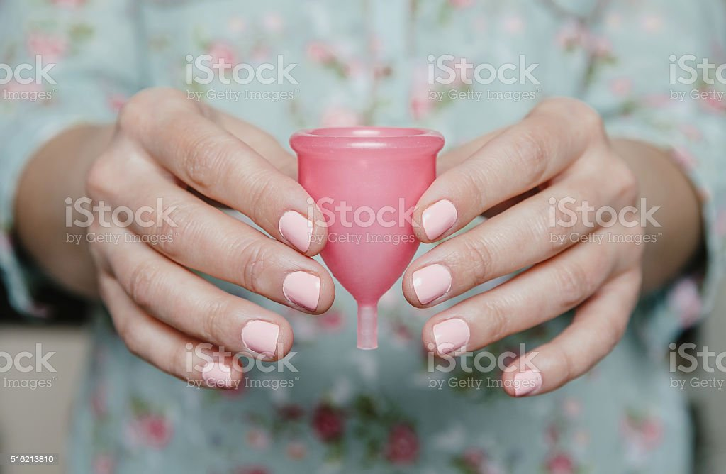 Close up of woman hands holding menstrual cup stock photo