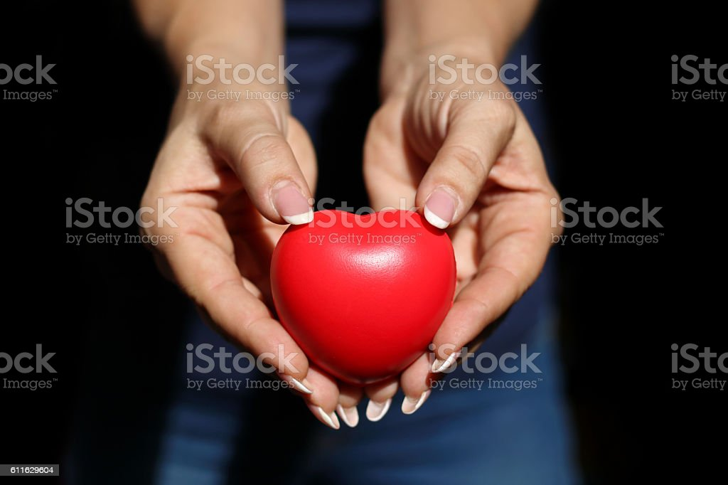 close up of woman  hands showing red heart stock photo