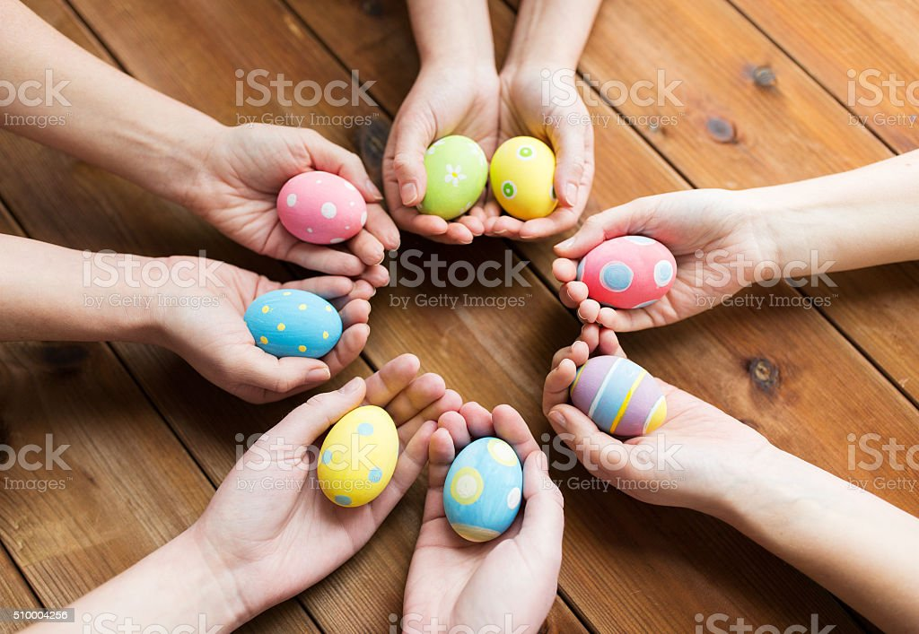 close up of woman hands with colored easter eggs stock photo