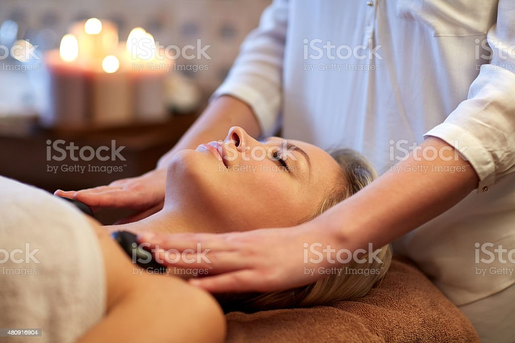 close up of woman having hot stone massage in spa stock photo