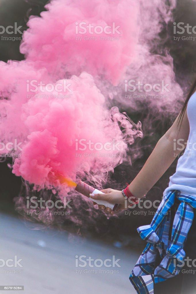 Close up of woman holding a smoke bomb stock photo