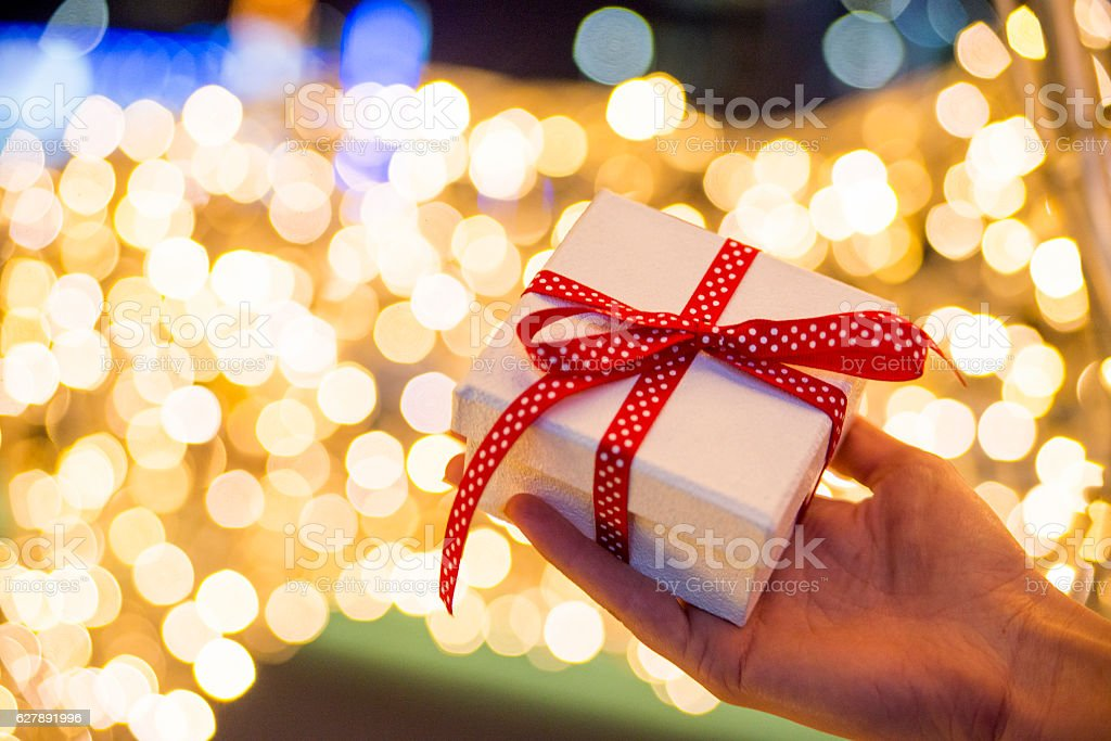 Close up of Woman holding gift box against Cozy Christmas stock photo