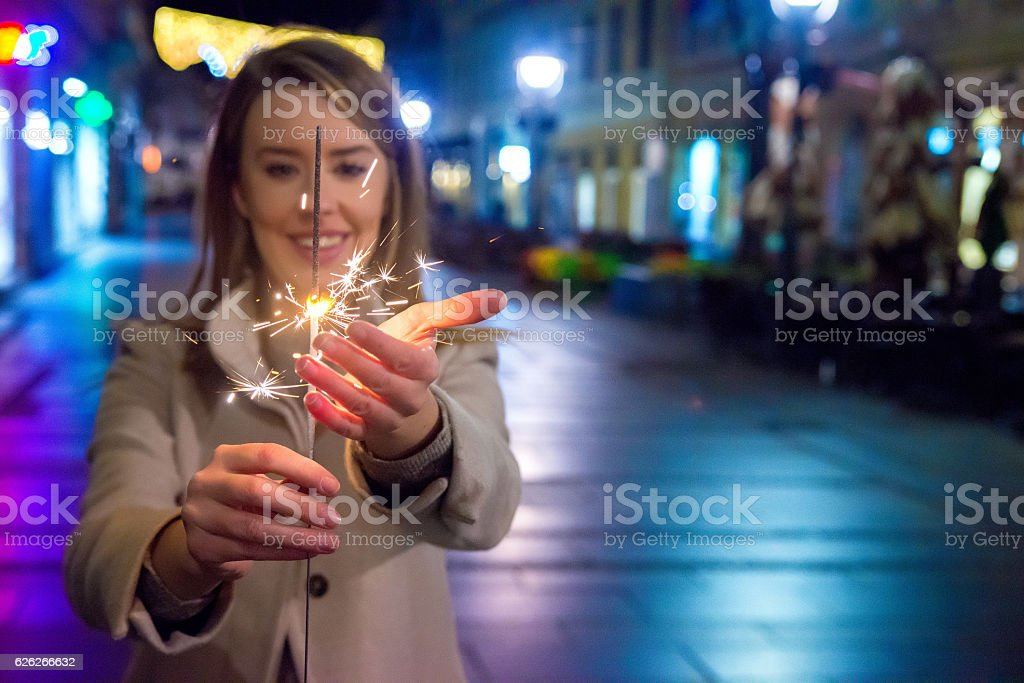 Close up of woman  holding sparkler at night stock photo