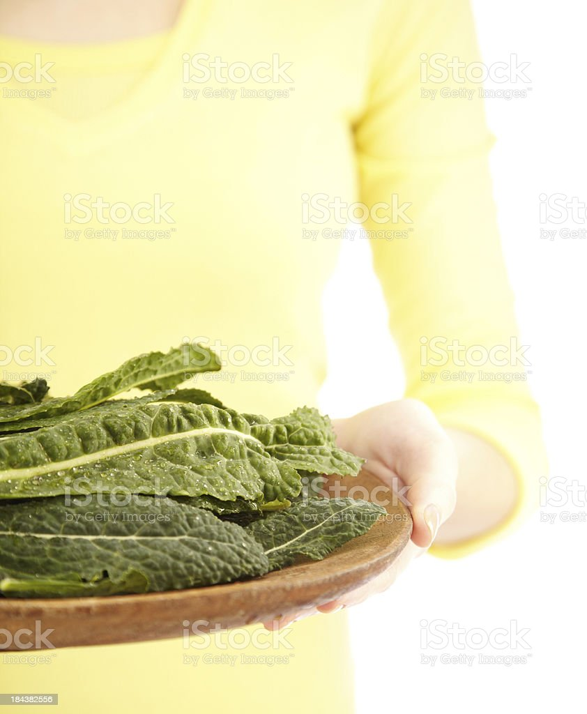 Close up of woman holding wooden tray containing green kale royalty-free stock photo