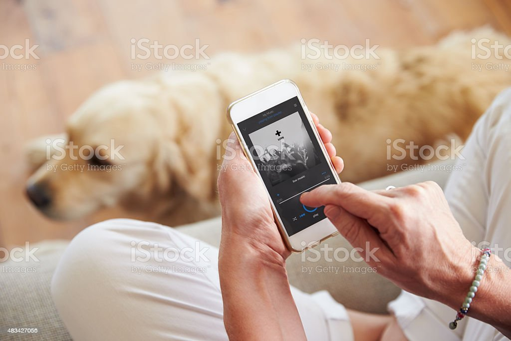 Close Up Of Woman Listening To Music Smartphone At Home stock photo