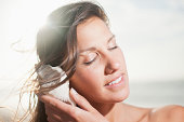 Close up of woman listening to seashell