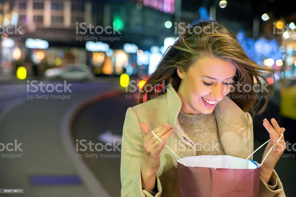 Close up of woman  looking at a gift bag stock photo
