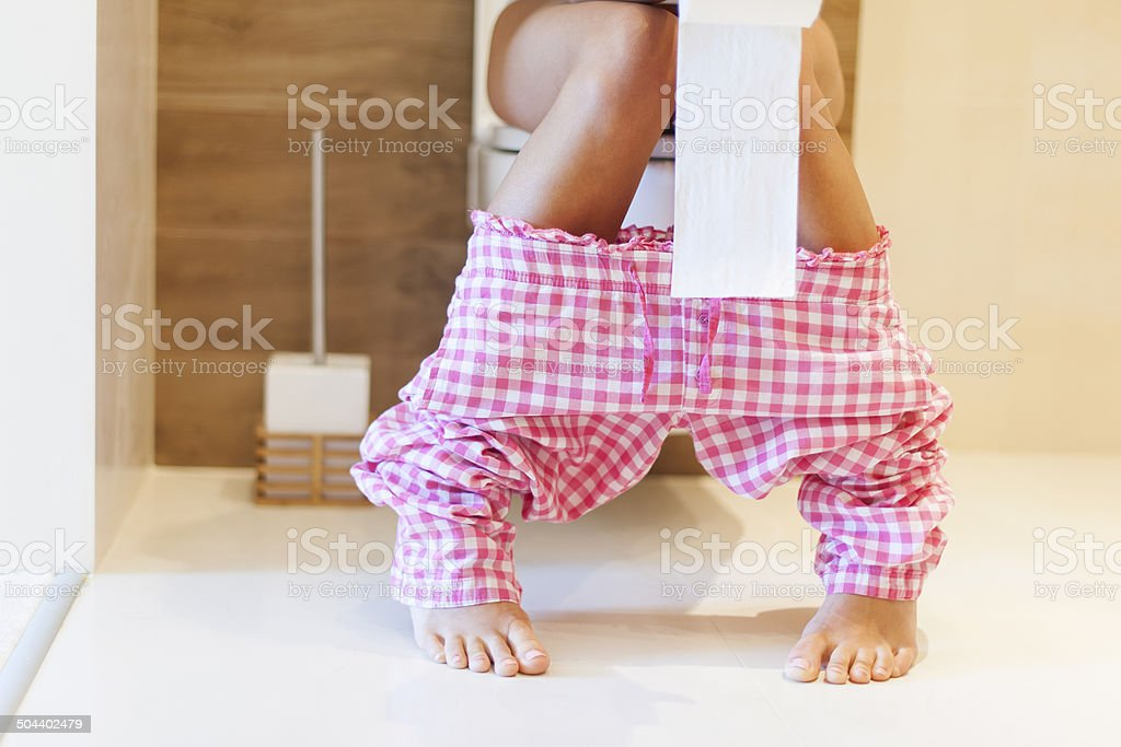 Close up of woman on toilet in morning stock photo