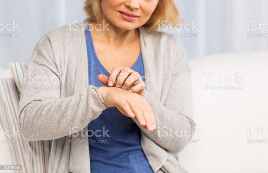 close up of woman suffering from hand inch at home stock photo