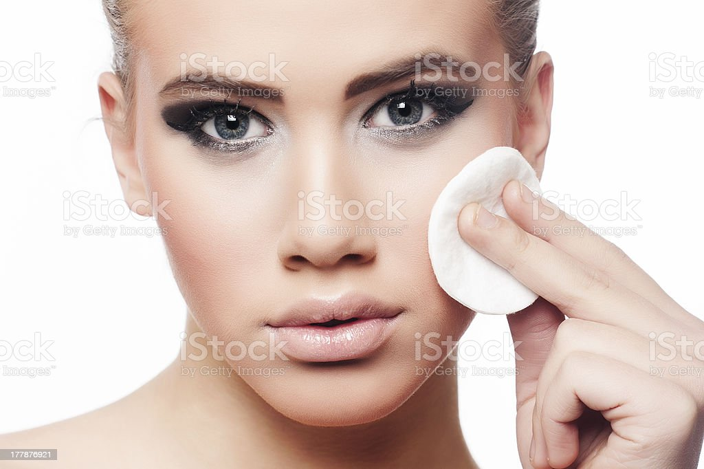 Close up of woman using cotton pad to remove make up stock photo