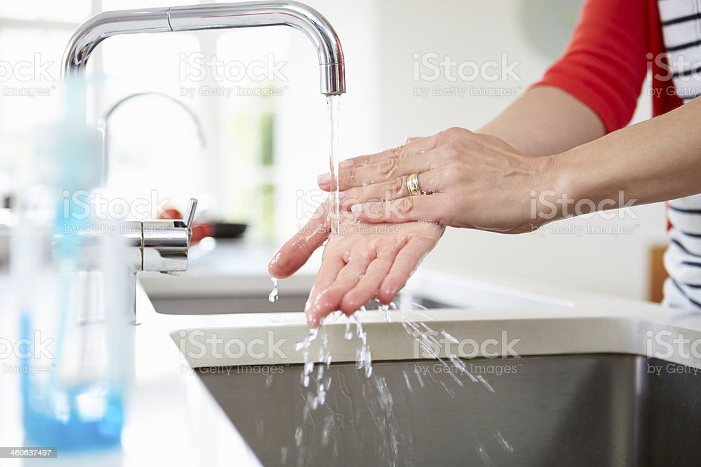 Close Up Of Woman Washing Hands In Kitchen Sink stock photo