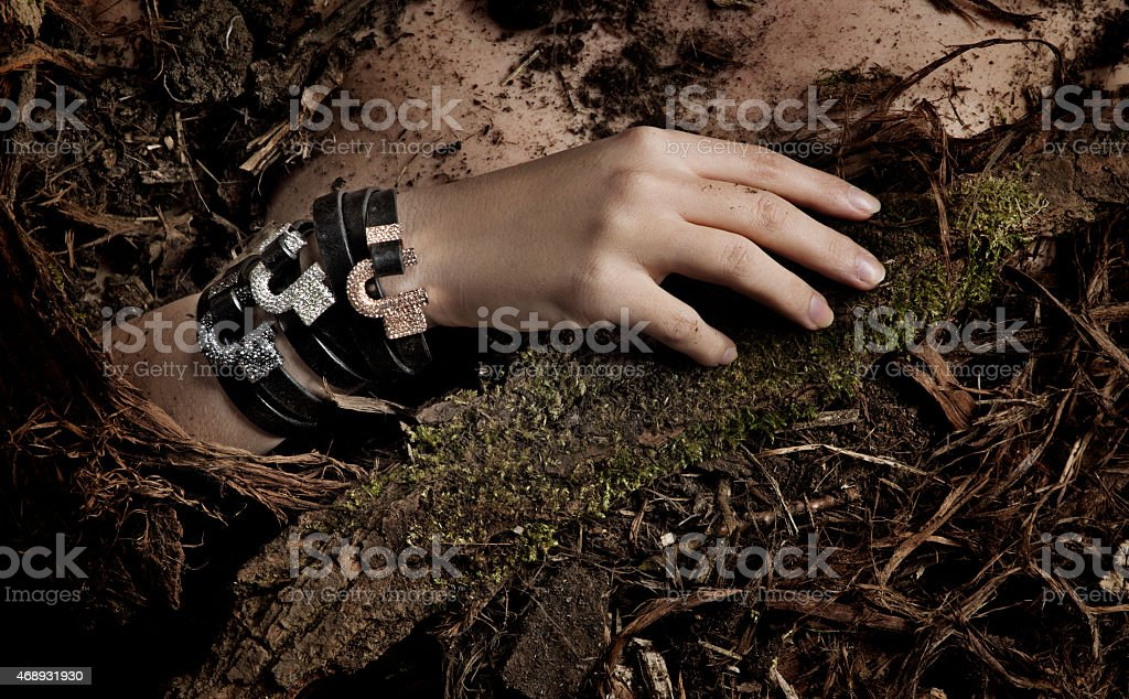 close up of woman wearing bracelets laying down in dirt stock photo