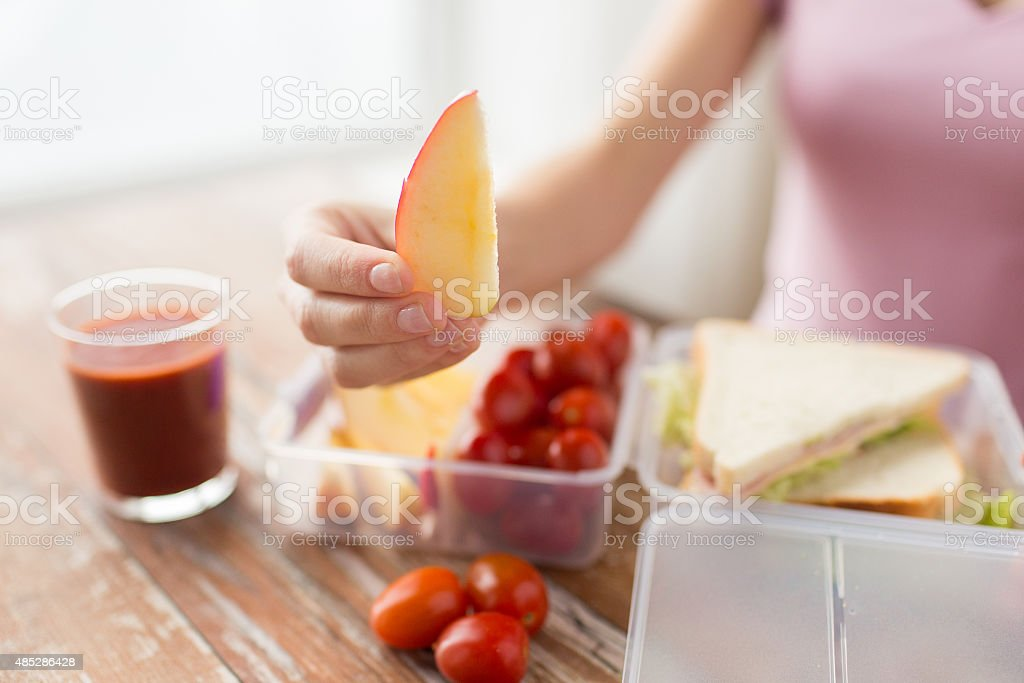 close up of woman with food in plastic container stock photo