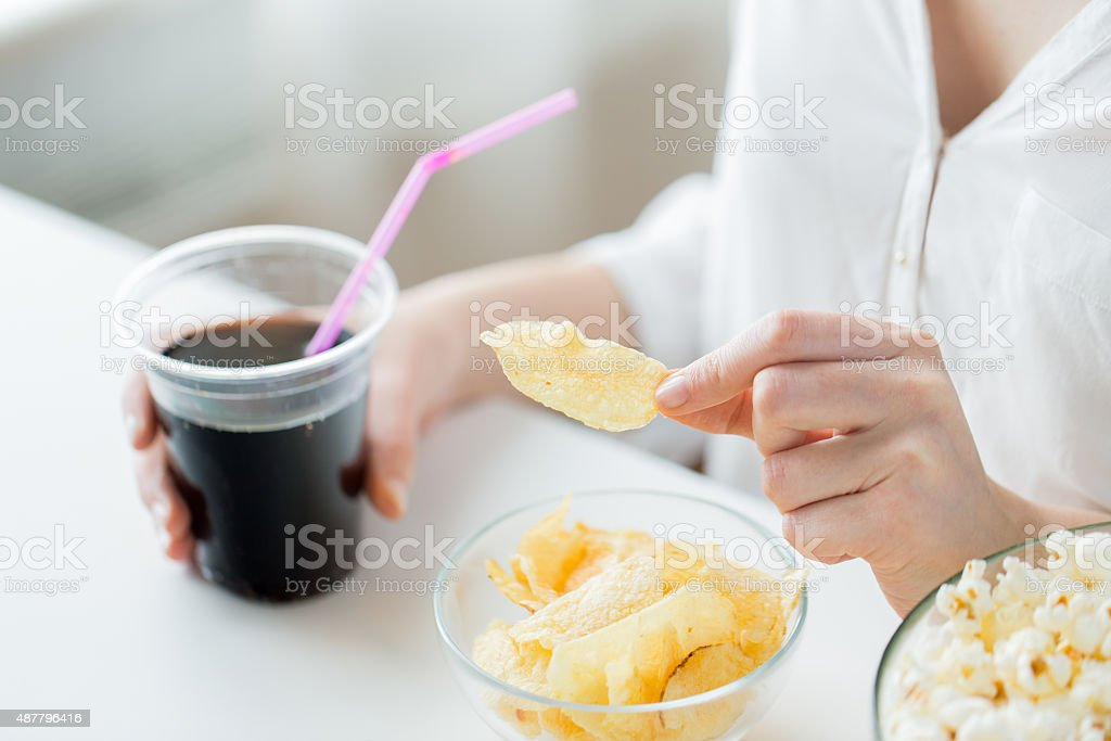 close up of woman with junk food and drink stock photo