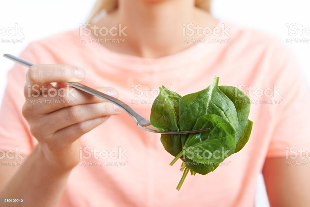 Close Up Of Woman With Spinach On Fork stock photo
