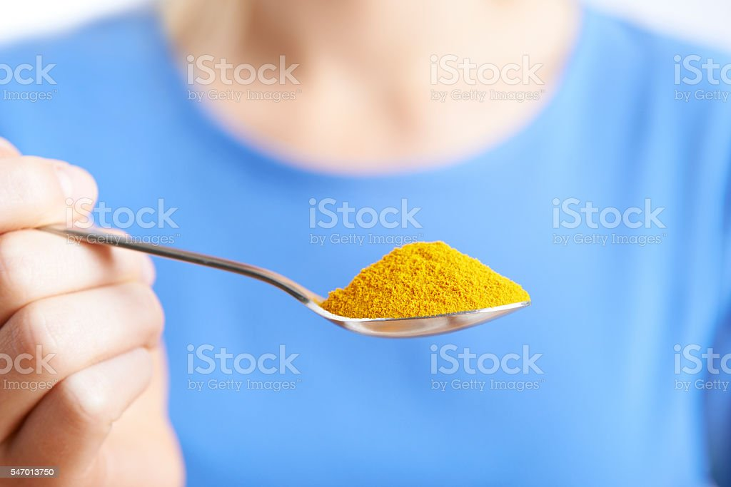 Close Up Of Woman With Spoonful Of Tumeric Powder stock photo