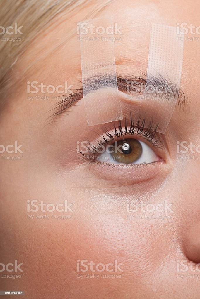 Close up of woman's eye taped open stock photo