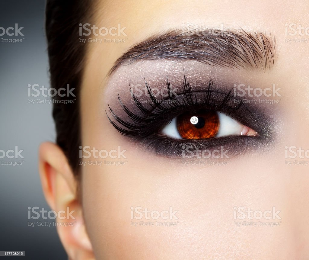 Close up of woman's eye with heavy make up and red iris stock photo