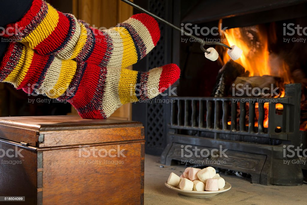 Close Up Of Womans Feet Relaxing By Cosy Log Fire stock photo