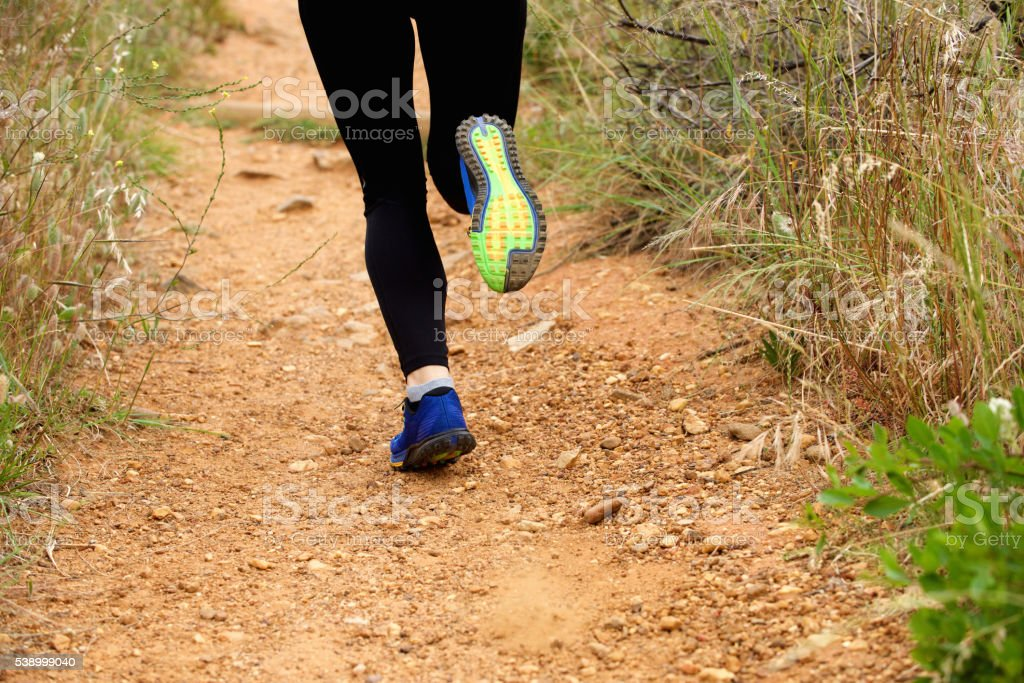 Close up of woman's feet running on footpath from behind stock photo