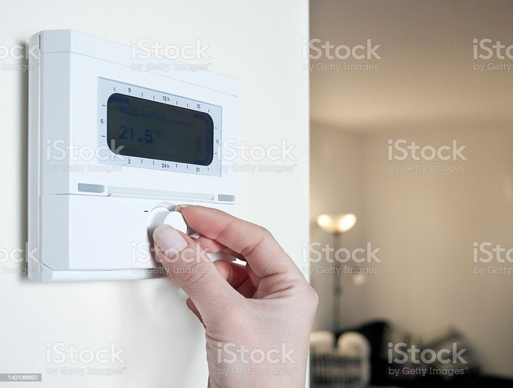 Close up of woman's hand adjusting the thermostat stock photo
