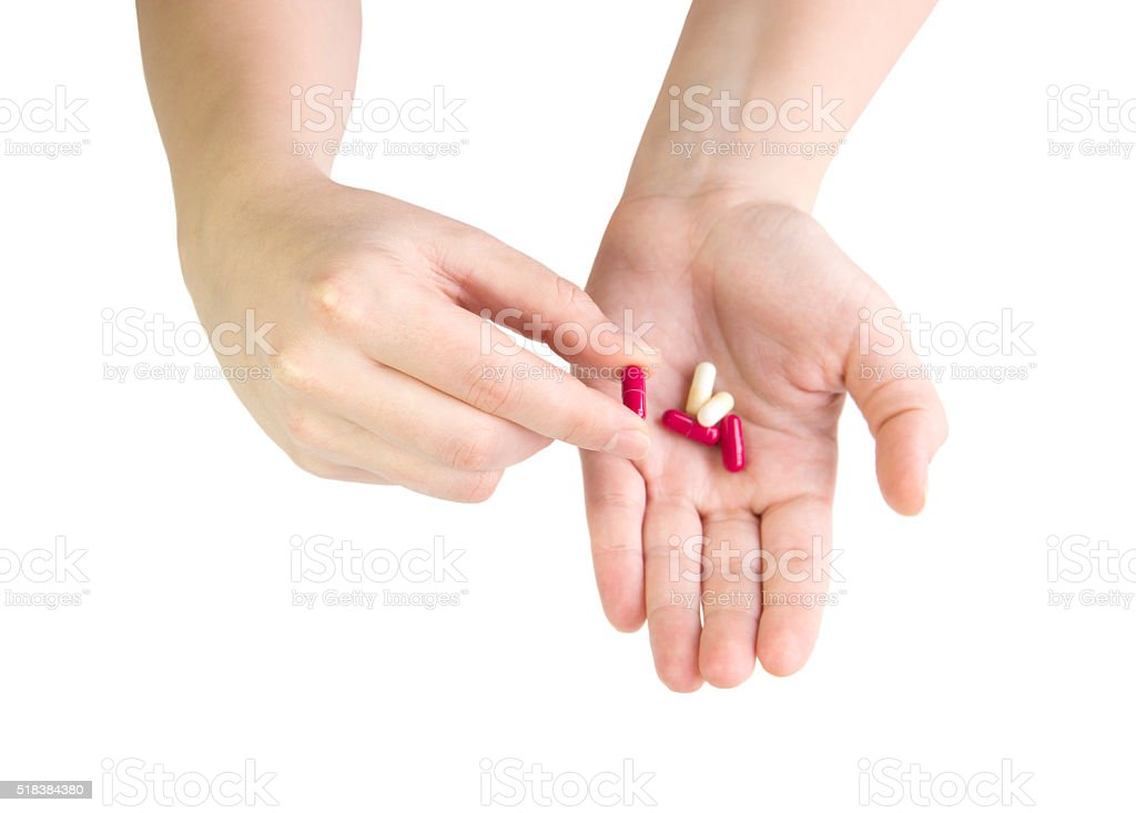Close up of woman's hand holding a red pill. stock photo