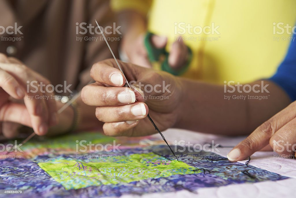 Close Up Of Woman's Hand Sewing Quilt stock photo