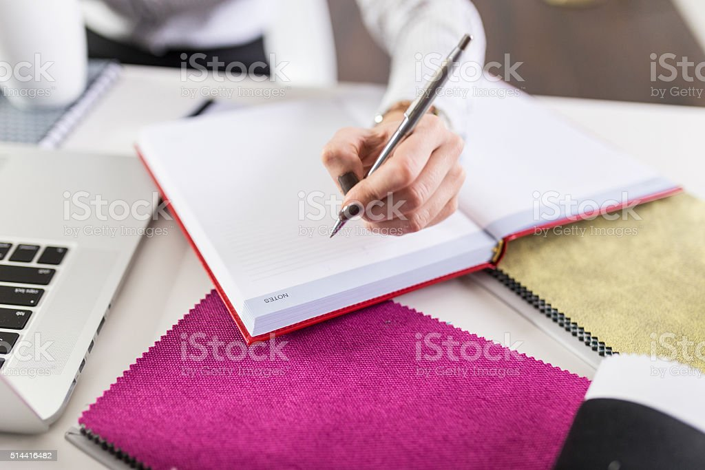 Close up of woman's hand writting notes in notebook stock photo