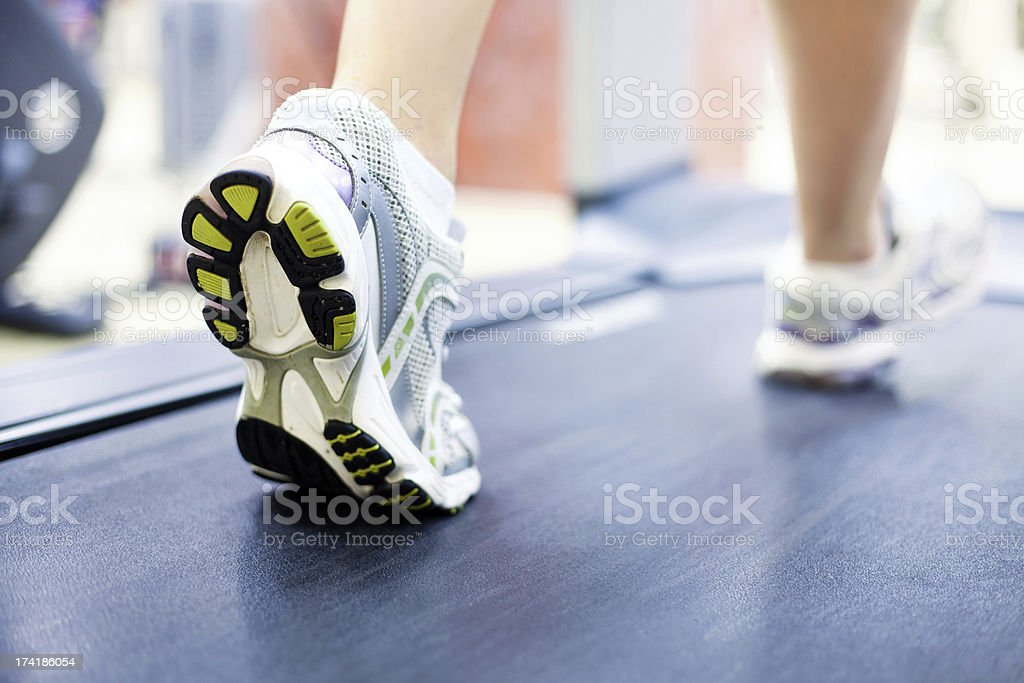 Close up of woman's legs with shoes on treadmill stock photo
