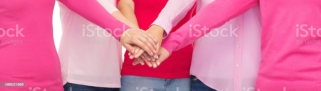 close up of women in pink shirts hands on top stock photo