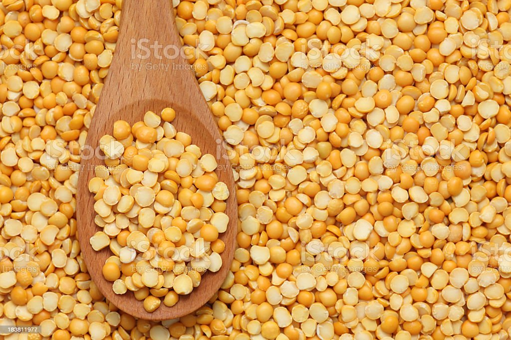 Close up of wooden spoon on pile of yellow split peas stock photo
