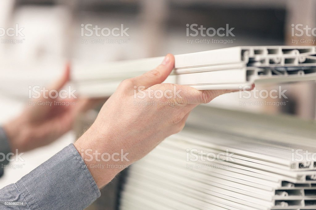 Close up of worker hands stacking plastic boards stock photo