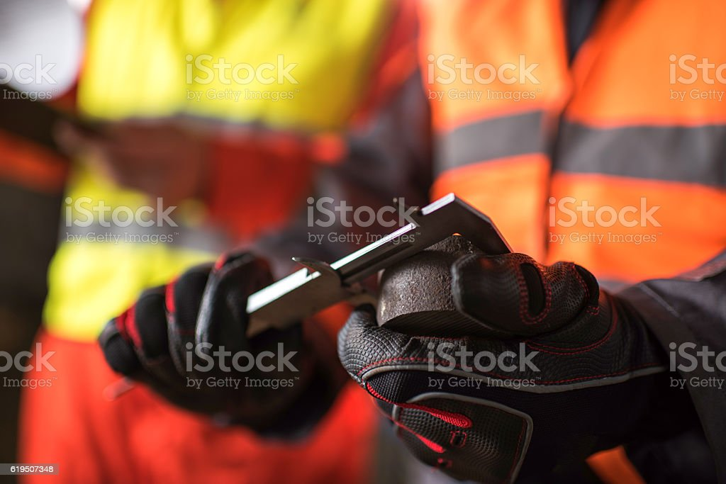 Close up of worker measuring steel with caliper. stock photo