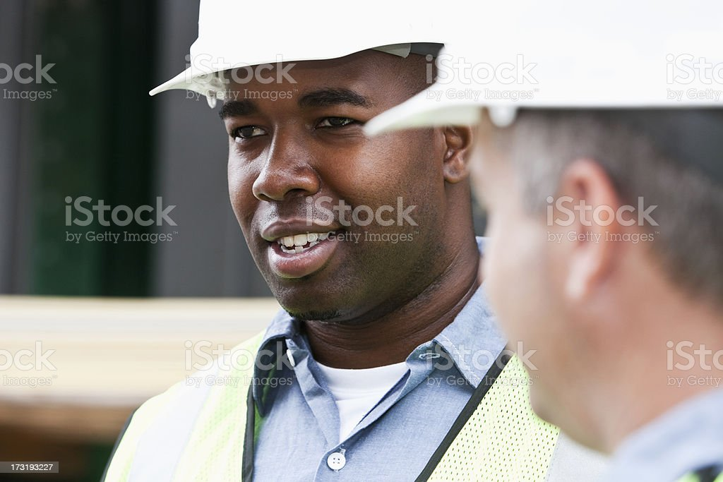 Close up of workers wearing hardhats and safety vests stock photo