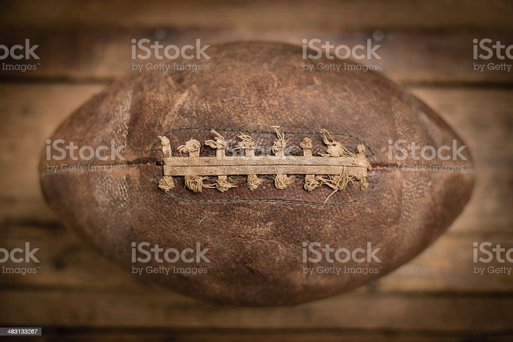 Close Up of Worn, Vintage Football Sitting on Wood Background stock photo
