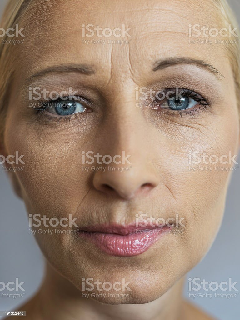 Close up of wrinkled mature woman looking at the camera. stock photo