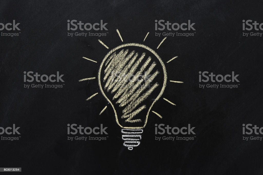 close up of yellow electric bulb drawn on black chalkboard stock photo