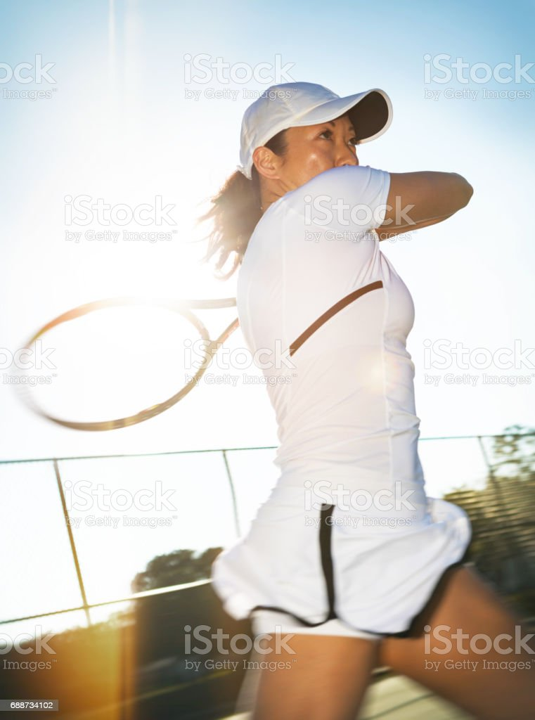 Close up of young asian woman tennis player hitting an open stance forehand stock photo