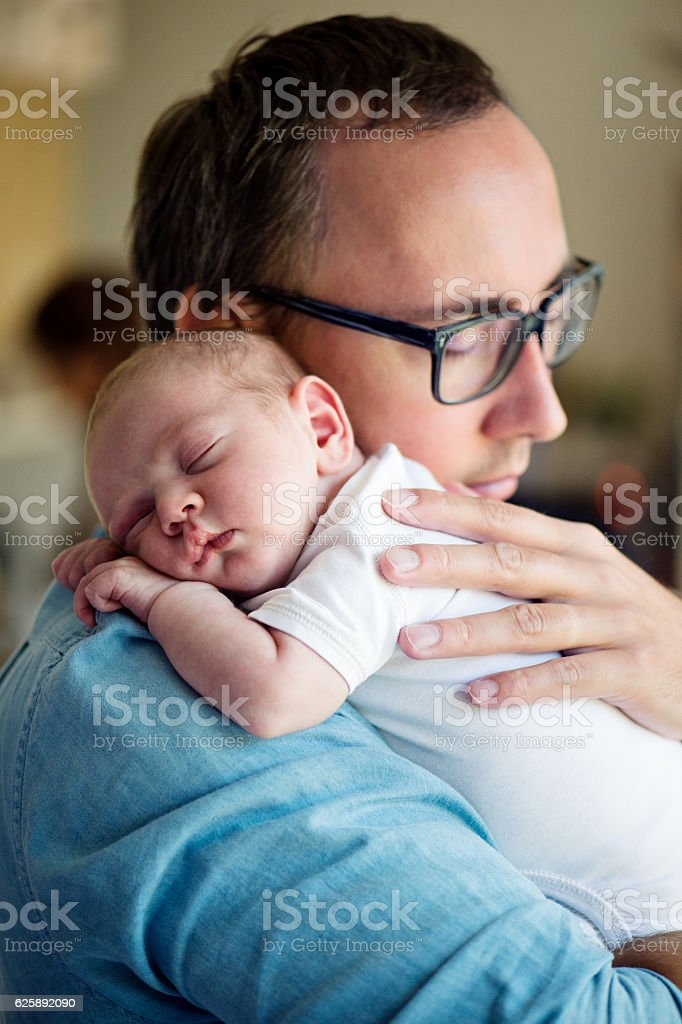 Close up of young father holding his newborn baby son stock photo